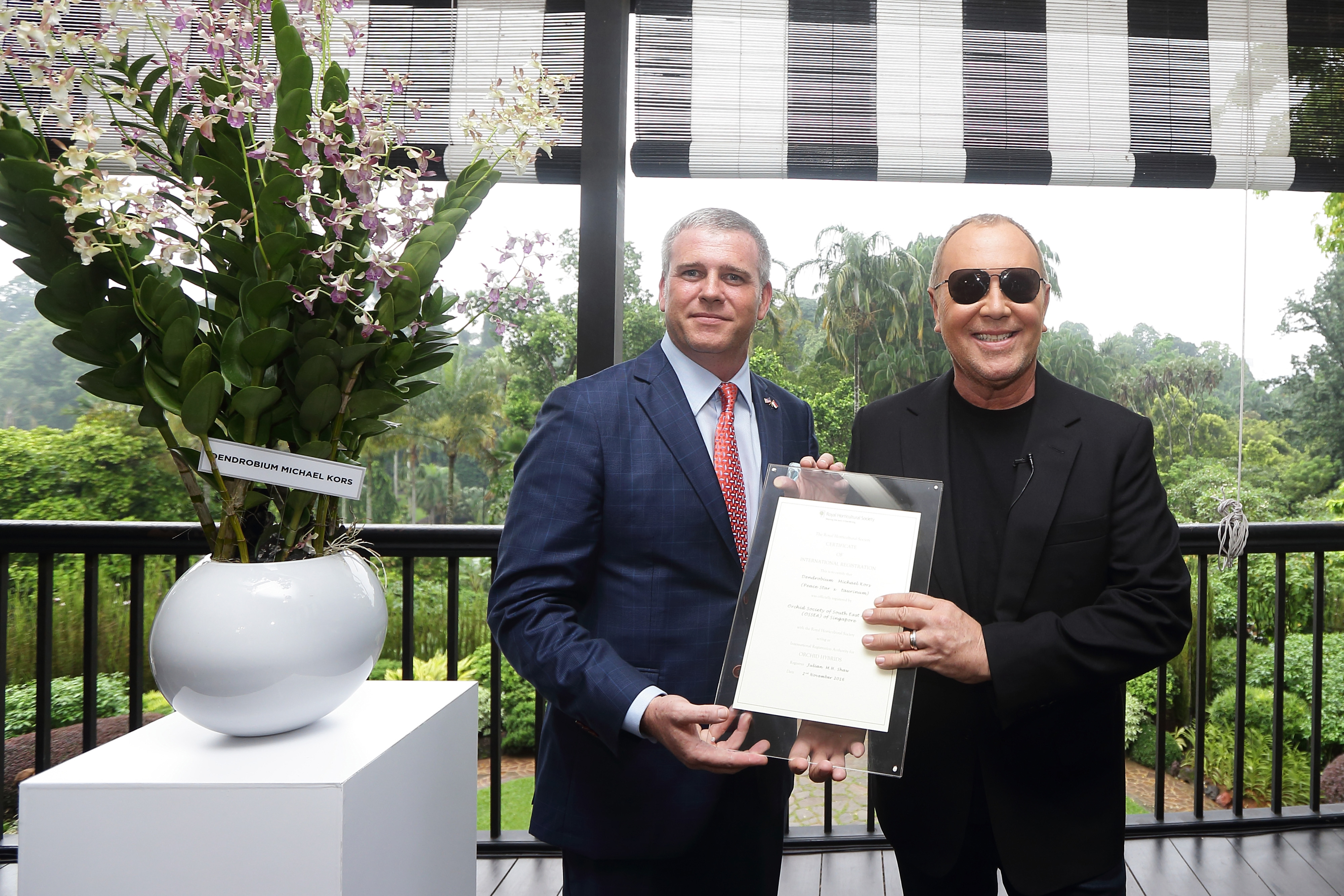 SINGAPORE - NOVEMBER 14: American designer, Michael Kors (R) received a plaque certificate from U.S. Ambassador, Kirk Wagar during the Michael Kors Orchid Naming Ceremony at the National Orchid Garden on November 14, 2016 in Singapore. (Photo by Suhaimi Abdullah/Getty Images for Michael Kors)