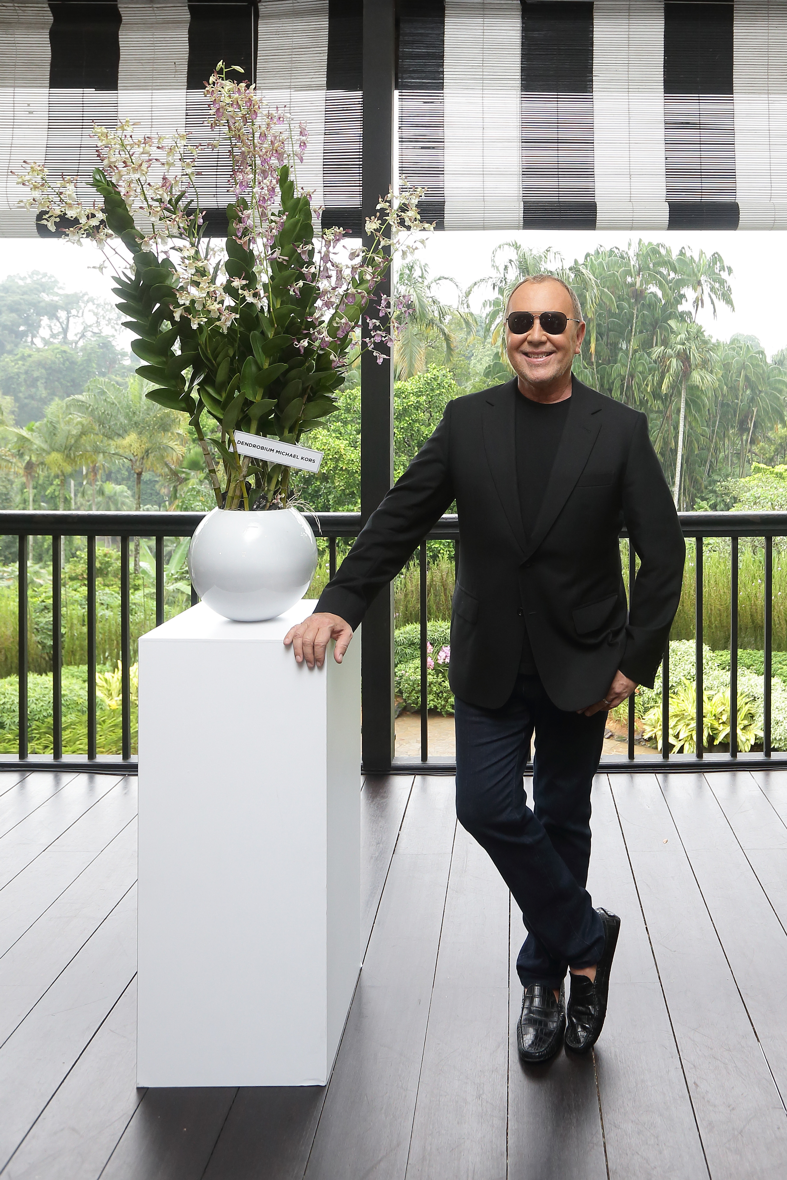 SINGAPORE - NOVEMBER 14: American designer, Michael Kors poses for a photo with the Dendrobium Michael Kors, an orchid that was named after him at the National Orchid Garden on November 14, 2016 in Singapore. (Photo by Suhaimi Abdullah/Getty Images for Michael Kors)